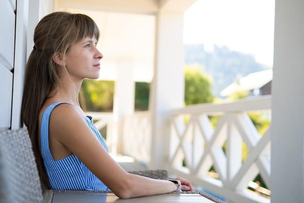 Vista laterale di bella donna castana in vestito blu che si siede sulla sedia lavorata a maglia. concetto di relax all'aria aperta sul balcone.