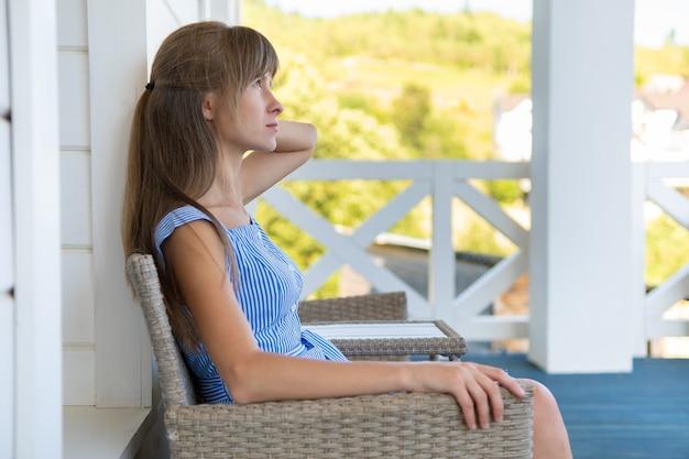 Vista laterale di una bella donna bruna in abito blu seduta su una sedia a maglia