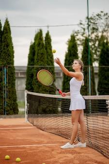Vista laterale di una donna bella e competitiva sorridente, mentre tiene la racchetta da tennis e la palla prima di iniziare la partita su un campo da tennis professionale.
