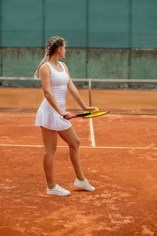 Vista laterale di una donna bella e competitiva sorridente, mentre si tiene la racchetta da tennis e la palla prima di iniziare la partita su un campo da tennis professionale
