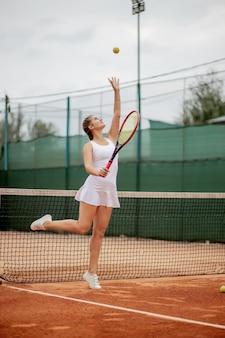 Vista laterale di una donna bella e competitiva sorridente, mentre si tiene la racchetta da tennis