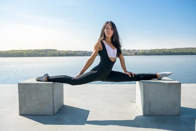 Vista laterale di un atleta di bella giovane donna europea facendo le spaccate mentre è seduto in una calda giornata estiva. concetto di stile di vita attivo di sport.