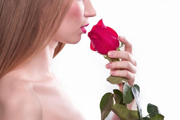 Vista laterale. una bella ragazza con una rosa rossa. isolato su sfondo bianco