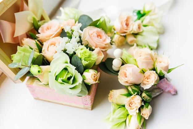 Vista laterale di una bella scatola di legno con rose e vicino boutonniere per lo sposo e i testimoni dello sposo