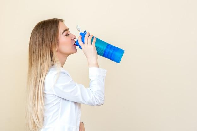 La vista laterale della bella giovane donna caucasica sta bevendo l'acqua dalla bottiglia di plastica
