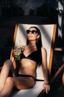 La vista laterale della bella giovane donna in occhiali da sole e costume da bagno tiene un bicchiere con cocktail, guardando il mare, sognando, mentre si riposa sul lettino di lusso