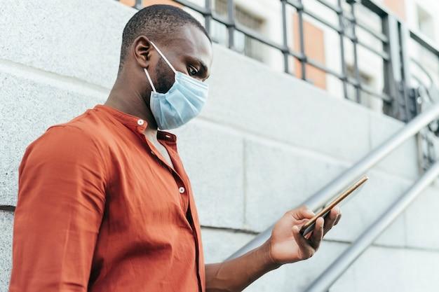 Vista laterale dell'uomo nero che indossa mascherina chirurgica e maglietta arancione. sta usando lo smartphone per strada