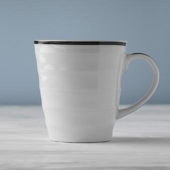 Vista laterale della tazza bianca in bianco sulla tavola bianca e sul fondo blu