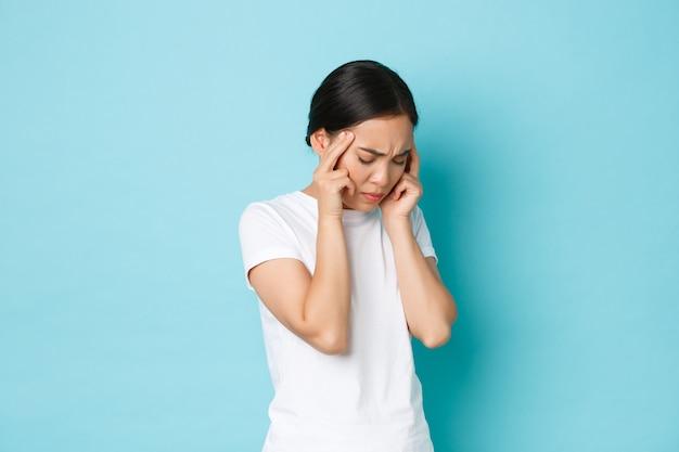 Vista laterale della ragazza asiatica stanca infastidita che fa smorfie, tocca la testa e si lamenta del mal di testa, ha dolore alla testa, emicrania o sensazione di vertigini, mal di parete blu in piedi