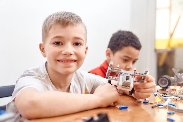 Vista laterale del kit di costruzione per un gruppo di bambini multirazziali che creano giocattoli. primo piano di amici che lavorano al progetto.