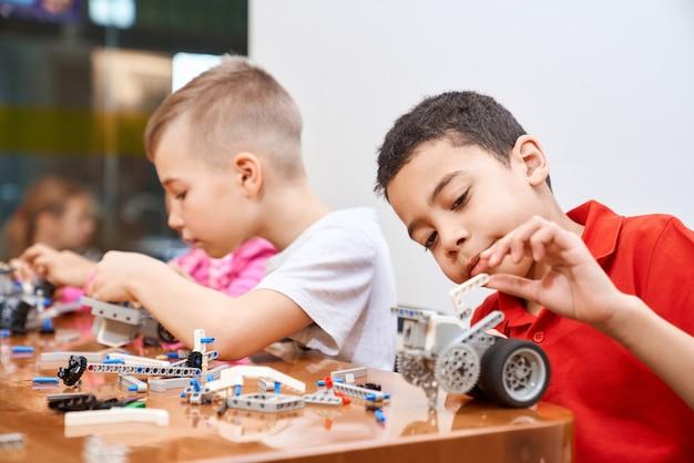 Vista laterale del kit di costruzione con pezzi colorati nella scatola per un gruppo di bambini multirazziali che creano robot, con emozioni positive e gioia.