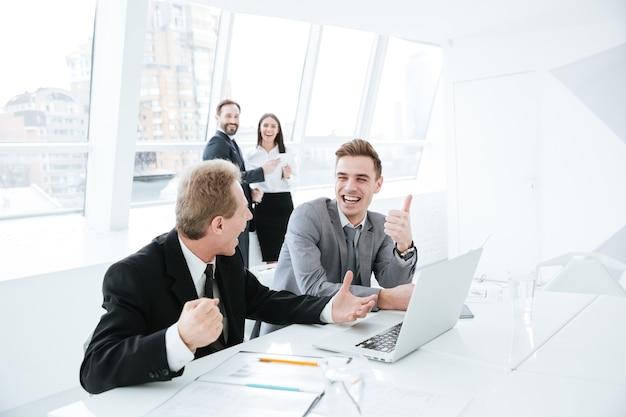 Vista laterale dei partner commerciali seduti al tavolo con laptop e documenti in sala conferenze con i colleghi