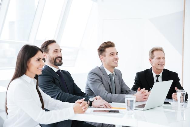 Vista laterale degli uomini d'affari seduti al tavolo nella sala conferenze