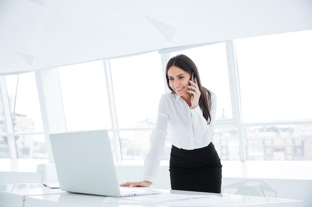 Vista laterale della donna d'affari in piedi vicino al tavolo, guardando il laptop e parlando al telefono in ufficio
