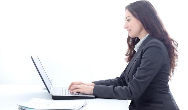 Vista laterale. donna d'affari che digita su un computer portatile.