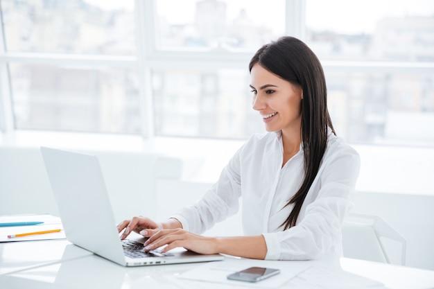 Vista laterale della donna d'affari che usa il laptop e si siede al tavolo in ufficio