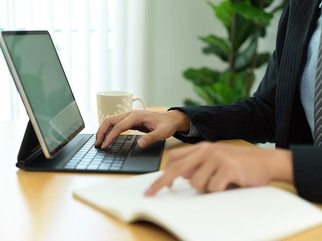 Vista laterale della mano dell'uomo d'affari che indica sul taccuino e digitando sulla tastiera del tablet nella stanza dell'ufficio