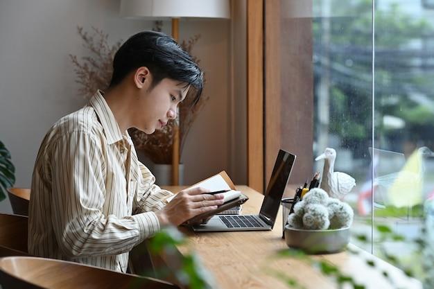Uomo d'affari di vista laterale che si siede davanti al computer portatile e che legge le informazioni sul taccuino.