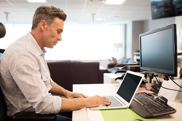 Vista laterale dell'uomo d'affari utilizzando laptop in ufficio