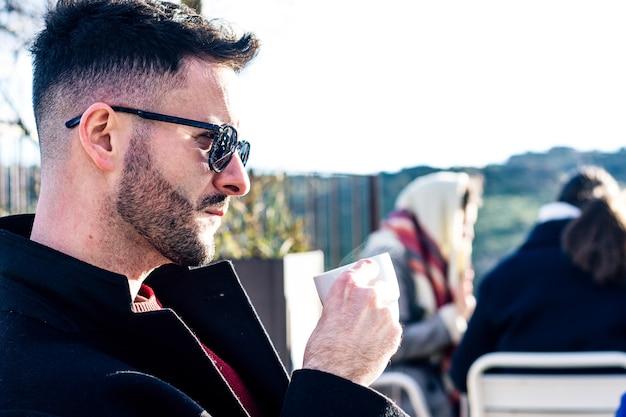 Vista laterale di un uomo d'affari con barba rifilata e occhiali da sole con un caffè sulla terrazza di un bar. persone sfocate sullo sfondo.