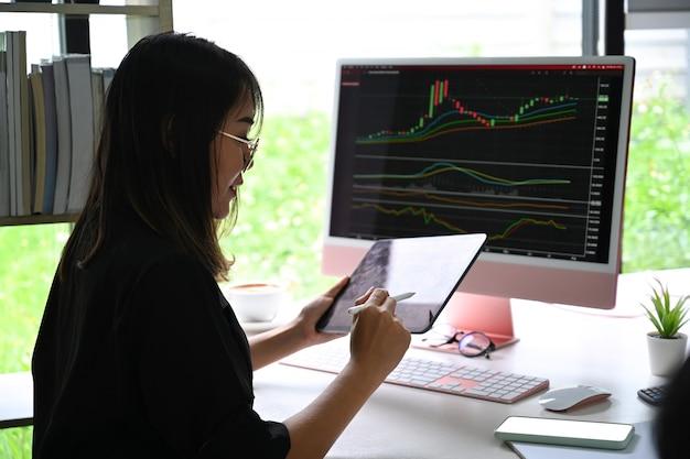 Donna di affari di vista laterale che analizza investimento del mercato azionario con la compressa digitale.