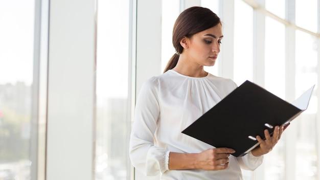 Vista laterale della donna di affari che esamina legante