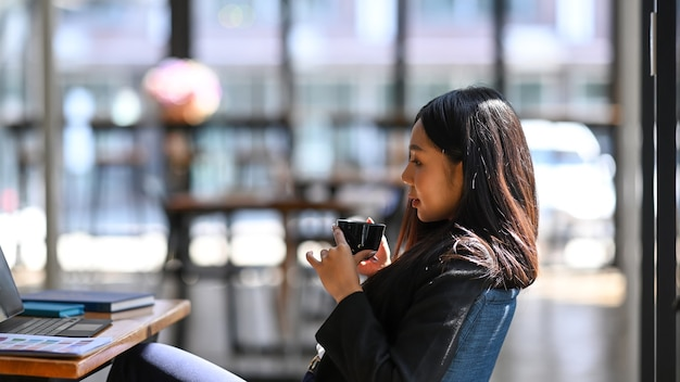 Vista laterale della donna di affari che prende una pausa e che beve caffè