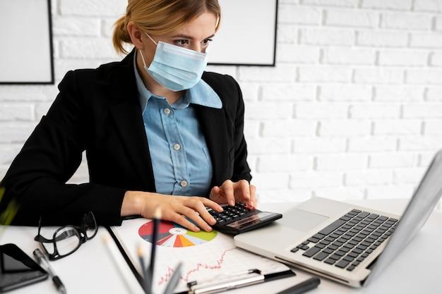 Vista laterale della donna di affari con la mascherina medica che lavora nell'ufficio con il computer portatile