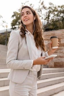 Vista laterale della donna di affari che lavora con lo smartphone e che mangia caffè