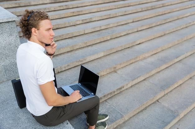 Vista laterale dell'uomo di affari riccio calmo che parla dallo smartphone mentre era seduto vicino alle scale con il computer portatile