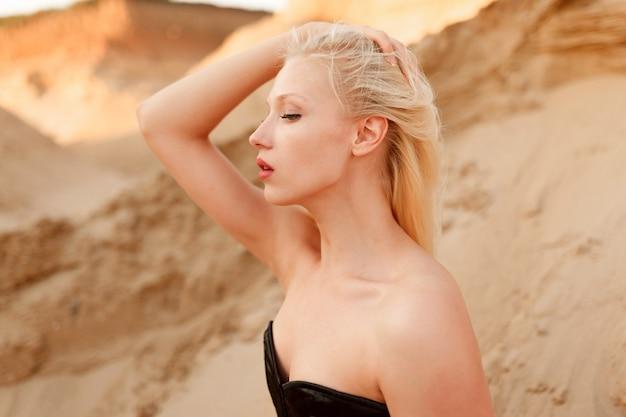 Vista laterale di un modello femminile caucasico con capelli biondi e trucco, in tuta sexy nera, toccando i suoi capelli, seduto sulla sabbia nel deserto.