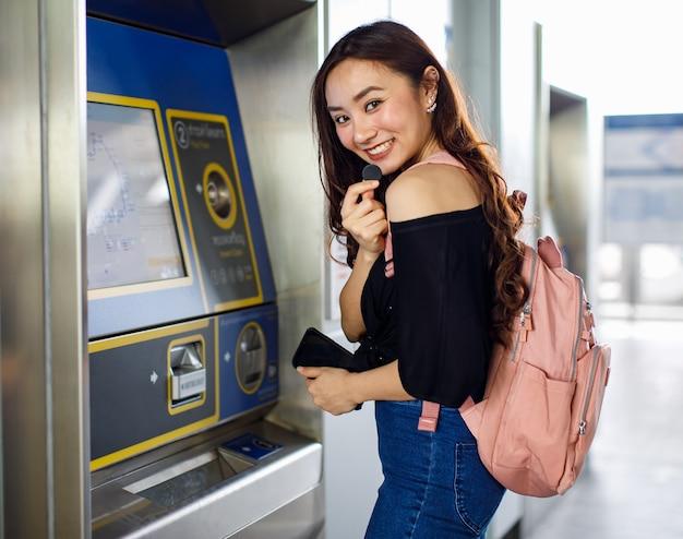 Vista laterale della passeggera etnica allegra che acquista il biglietto nel terminal della metropolitana e guarda la telecamera