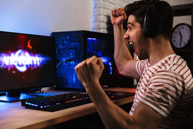 Vista laterale del giocatore allegro che gioca ai videogiochi sul computer