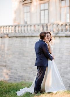 Vista laterale dello sposo e della sposa allegri, in piedi vicino all'architettura antica, tenendosi per mano e godendosi i loro felici momenti romantici