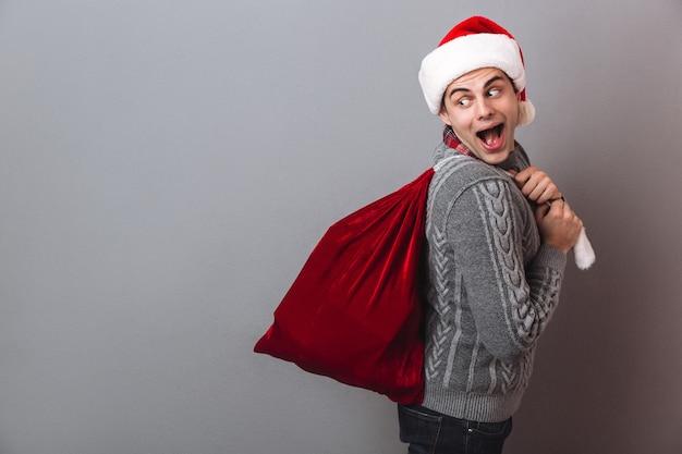 Vista laterale dell'uomo allegro in maglione e cappello di natale che tiene la borsa con regali e guardando indietro