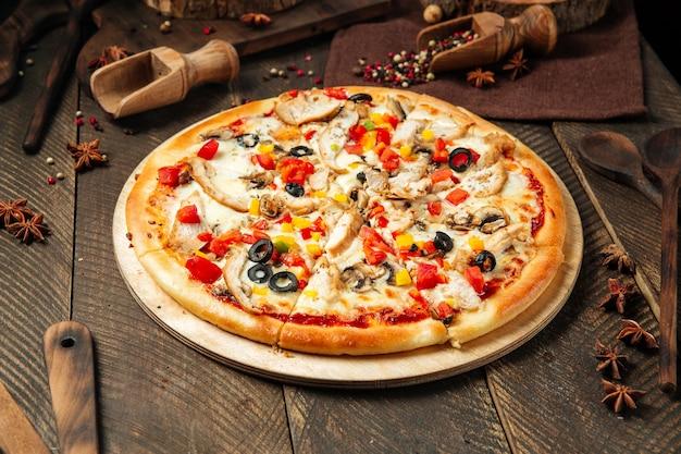 Vista laterale sulla pizza di pollo con funghi e verdure sul tavolo di legno