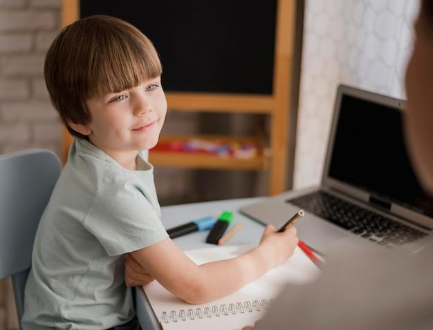 Vista laterale del bambino che impara a casa con il tutor