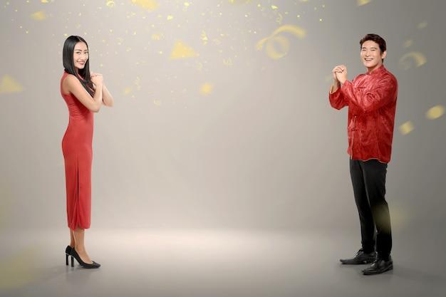 Vista laterale delle coppie cinesi in vestito tradizionale con confett