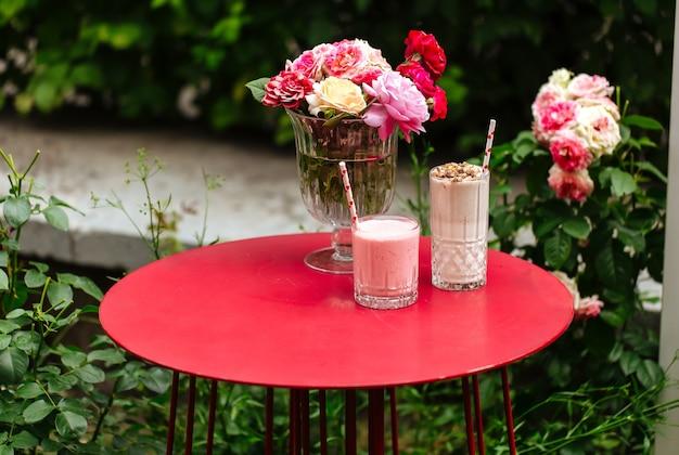 Vista laterale su frappè al cioccolato e fragola sul tavolo rosso
