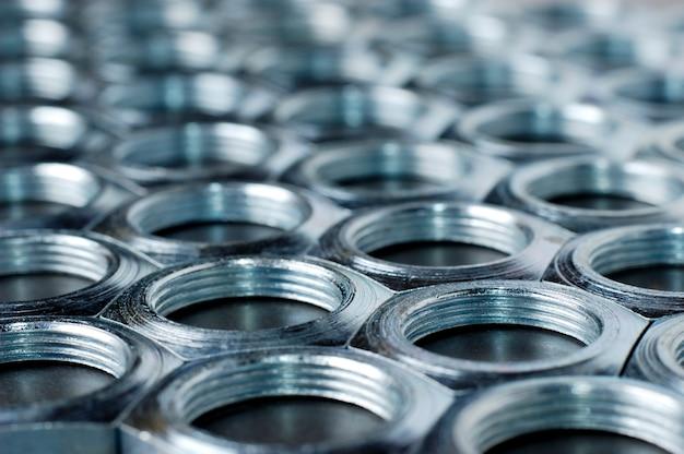 Vista laterale close-up cromo dadi in metallo a forma di favi si trovano uno accanto all'altro formando un'area. il concetto di elementi di fissaggio e costruzione. concetto di riparazione e parti