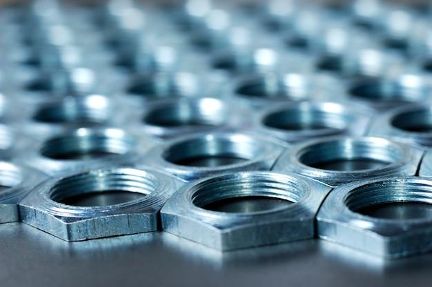 Vista laterale close-up di dadi in metallo cromato a forma di favi giacciono uno accanto all'altro