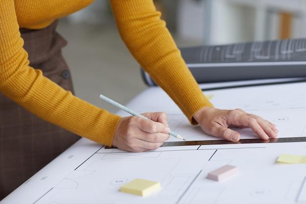 Vista laterale ravvicinata di un irriconoscibile architetto femmina cianografie di disegno mentre si appoggia sulla scrivania al posto di lavoro,