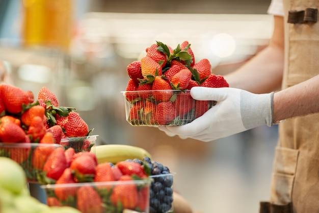 Vista laterale ravvicinata di un uomo irriconoscibile che tiene la scatola di deliziose fragole fresche al banco di frutta e verdura nel mercato degli agricoltori