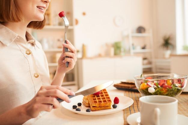 Vista laterale ravvicinata di una donna irriconoscibile che mangia delizioso dessert mentre era seduto da solo al tavolo da pranzo