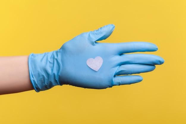 Vista laterale del primo piano della mano umana in guanti chirurgici blu che tengono in mano una piccola forma di cuore rosa