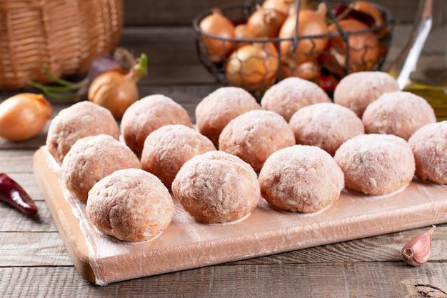 Primo piano di vista laterale sulle polpette congelate semilavorate crude sulla tavola di legno con riso, cipolla e carne, orizzontale