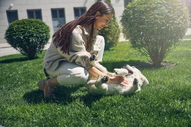 Vista laterale di una giovane donna contenta che gioca con il suo simpatico cane sull'erba verde
