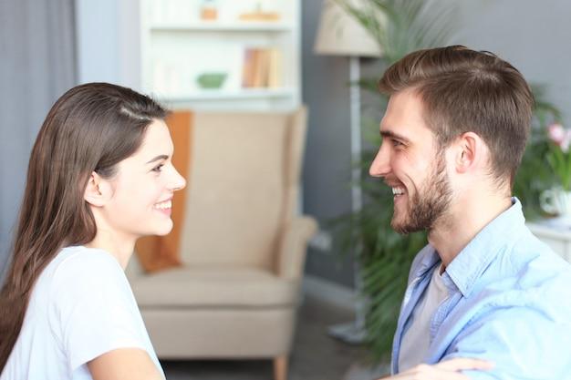 Vista laterale di una coppia che parla seduto su un divano e si guarda a casa.