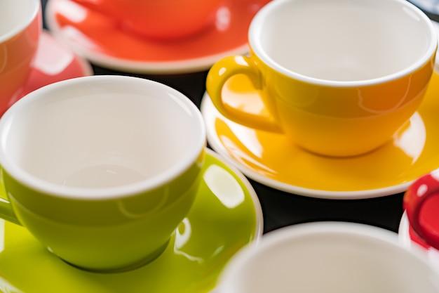 Vista laterale tazza di caffè colori alternati colorati è verde brillante per lo sfondo nella caffetteria