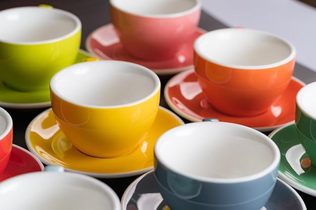 Vista laterale tazza di caffè colori alternati colorati e piattino per lo sfondo nella caffetteria